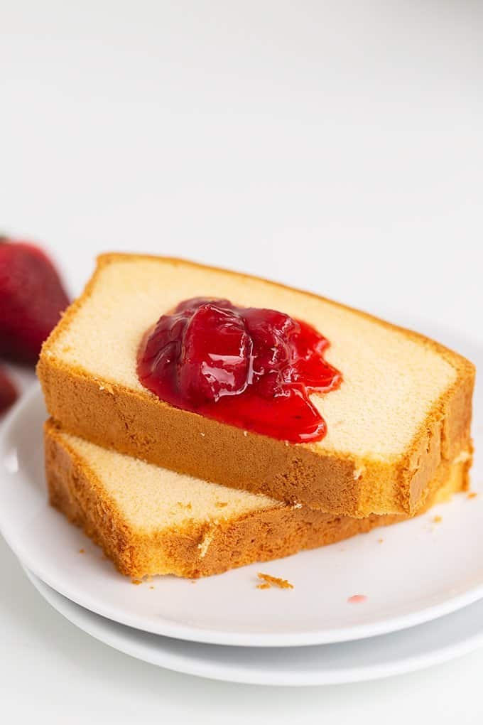 two slices of vanilla pound cake with a drizzle of strawberry syrup on top on a white plate