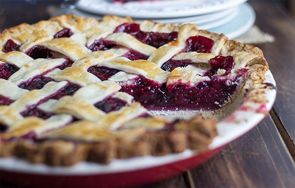 close up image of a lattice crust fruit pie made with blueberries, blackberries, and raspberries