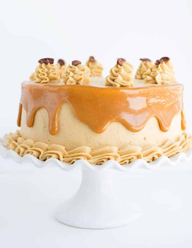 Side shot of carrot cake with caramel buttercream on a white ruffled cake plate.
