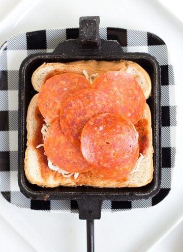 adding pepperoni to a pizza mountain pie maker