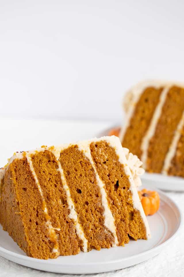 2 slices of pumpkin cake on their sides on white dessert plates