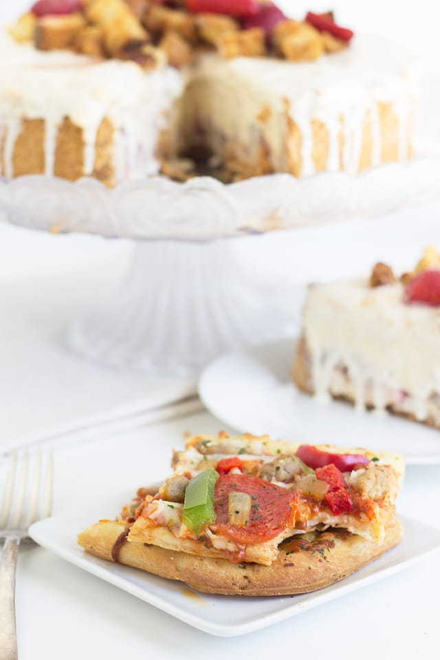 slice of pizza on a small plate in the foreground, Strawberry Shortcake Cheesecake on a cake stand in the background
