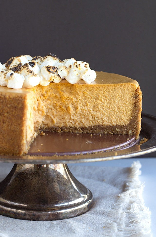 Sweet Potato Cheesecake topped with toasted mini marshmallows on a sliver cake stand. Cake has been sliced so that the center is exposed