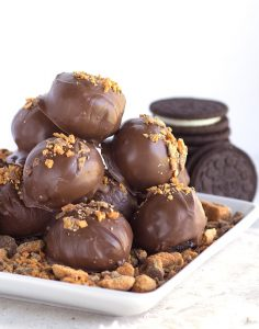 stack of butterfinger bites with crushed candy bars and white square plate with a stack of cookies