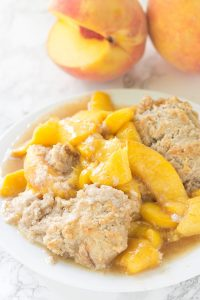 Skillet Peach Cobbler - fresh peaches sliced thrown in a skillet and topped with the perfect biscuit. This tastes amazing warmed with a scoop of vanilla ice cream!