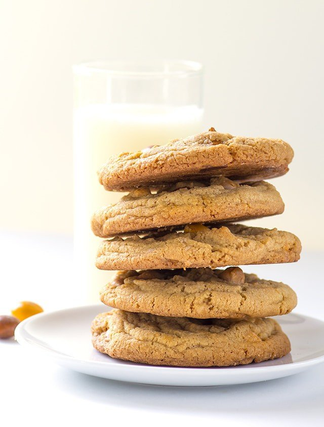stack of homemade Butterscotch Cookies on a plate with a tall glass of milk behind it