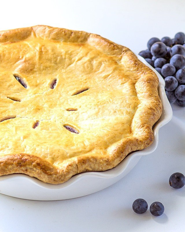 Concord Grape Pie baked in a white ceramic pie dish
