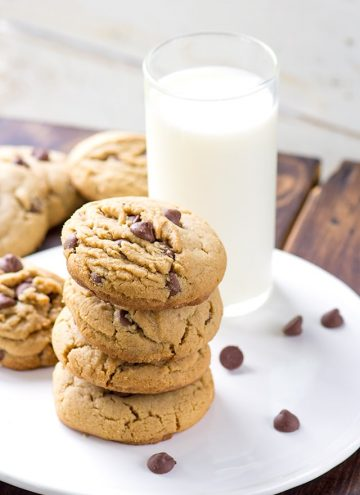 thick soft peanut butter chocolate chip cookies next to a glass of milk