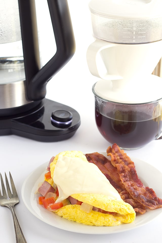 western omelet and bacon on a white plate with a fork and a coffee