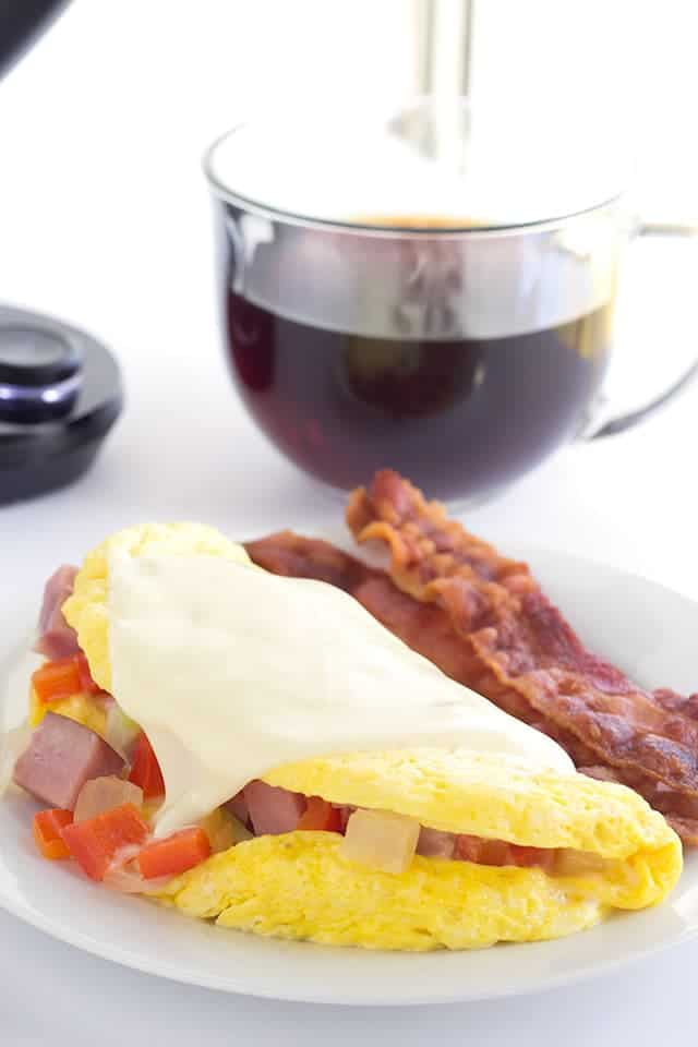 western omelet and bacon on a white plate with a cup of coffee behind it