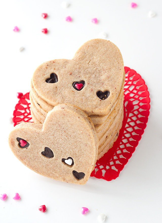 Strawberry Sugar Cookies - Delicious cut-out strawberry flavored sugar cookies with little heart cut outs that are filled with milk chocolate. The perfect Valentine's Day treat!