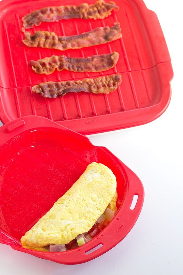 omelet in a red microwave dish with a bacon crisper next to it on a white surface