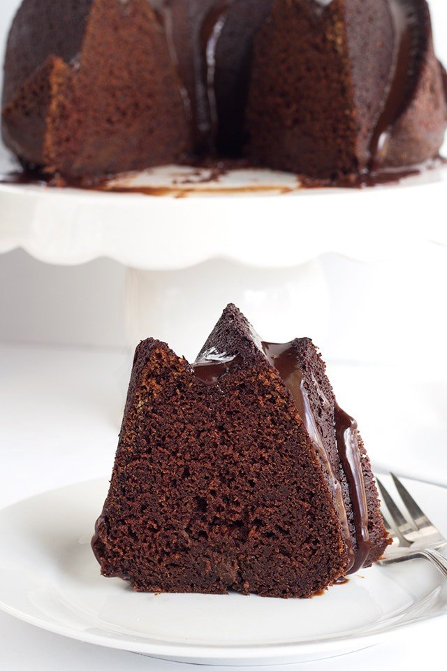 slice of Chocolate Whiskey Cake on a plate with the rest of the whiskey bundt cake on a cake plate behind it