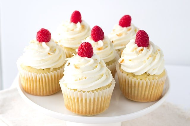 Coconut Cupcakes - coconut cupcakes stuffed with a homemade raspberry filling and topped with a high coconut frosting swirl