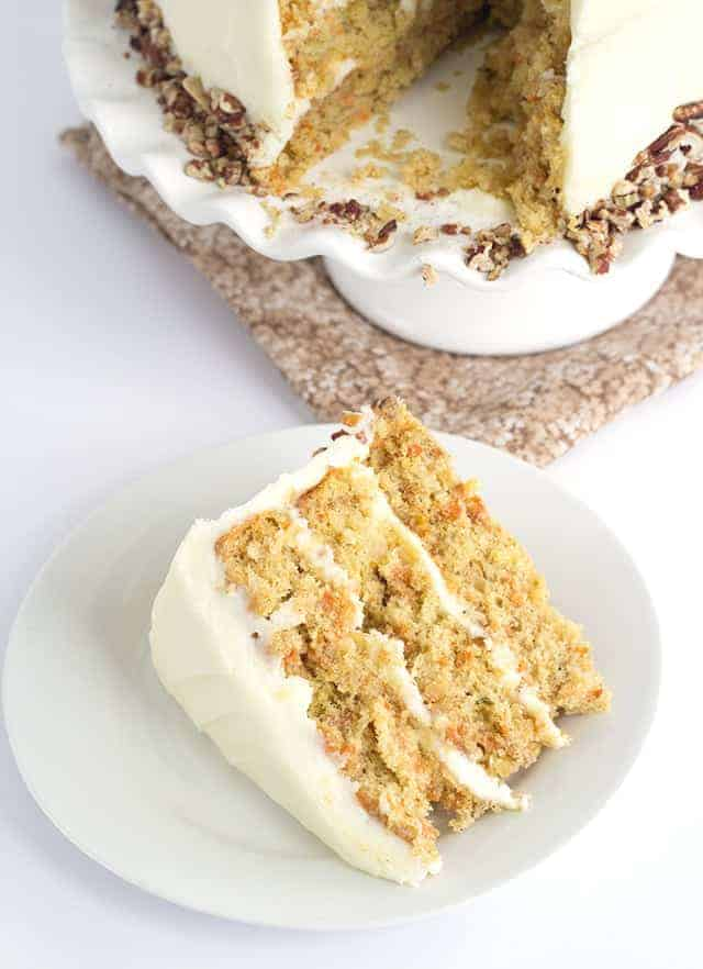 A slice of carrot layer cake with pineapple, topped with Cream Cheese Frosting