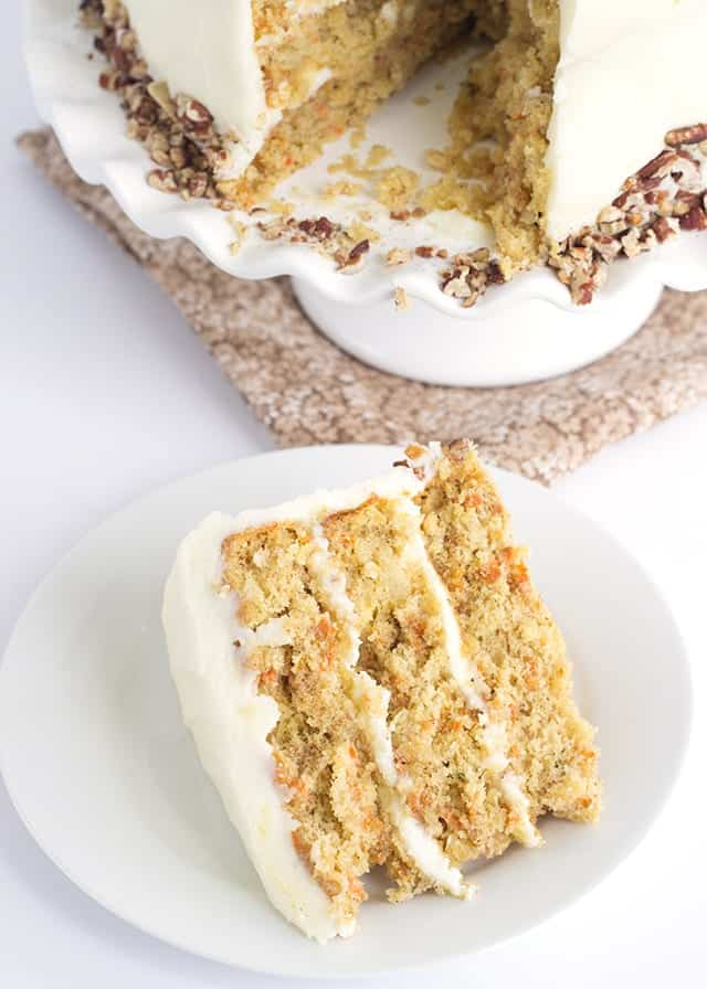Pineapple Carrot Cake with Cream Cheese Frosting - the perfect Easter cake! It's full of crushed pineapple, shredded carrots, and cinnamon. It's slathered with a cream cheese frosting infused with pineapple juice and garnished with toasted pecans.