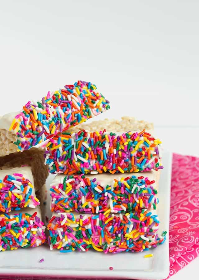 Chocolate Dipped Rice Krispie Treats on a plate with a pink fabric