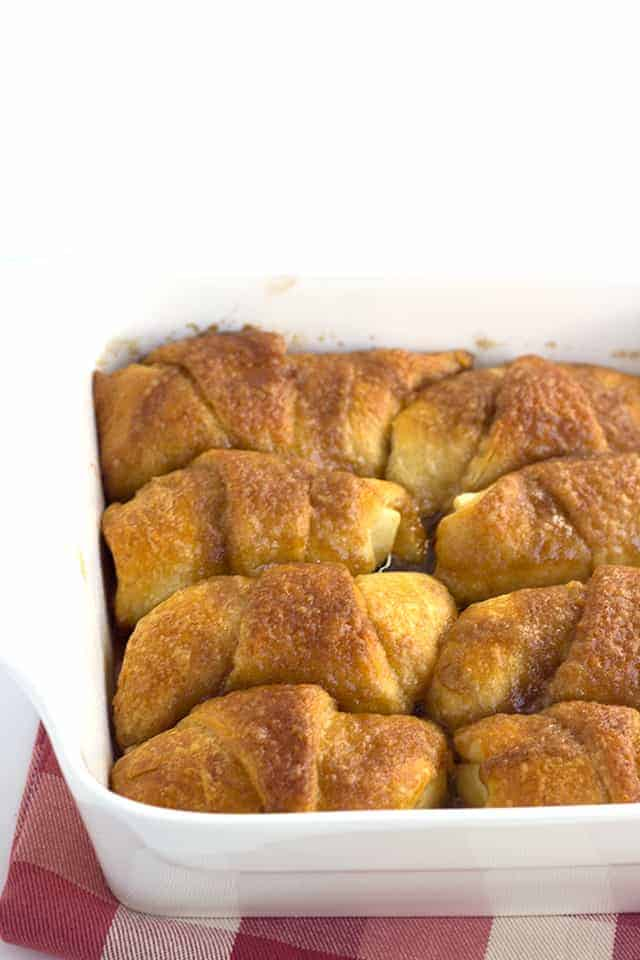 Crescent Roll Apple Dumplings - slices of apples rolled up in crescent rolls with cinnamon and sugar. Once everything is in the pan, it's coated with a layer of a buttery cinnamon brown sugar mixture and baked.