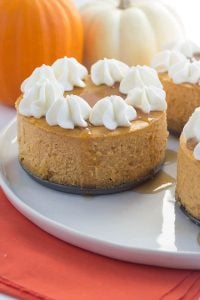 Mini Pumpkin Cheesecakes topped with maple syrup and whipped cream, sitting on a dessert platter