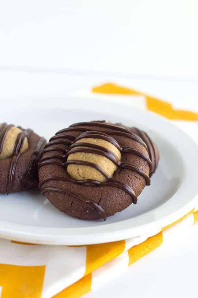 Buckeye Thumbprint Cookies - rich chocolate cookies stuffed with a sweet peanut butter ball and topped with a drizzle of chocolate! Everyone loves them!