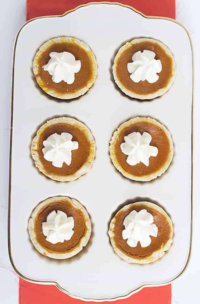 Mini Maple Pumpkin Pies - these adorable mini pumpkin pies have a hint of maple and loads of pumpkin spice! Top them with some fresh whipped cream and serve them at your next Thanksgiving get-together!