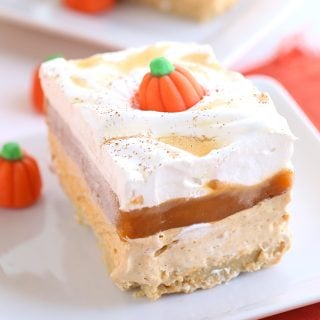 Pumpkin Butterscotch Layer Dessert - Layers of crushed vanilla sandwich cookies, pumpkin cheesecake, butterscotch pudding, whipped topping, and adorable candy pumpkins! This screams the perfect Fall and Thanksgiving dessert! It's so simple to make too!