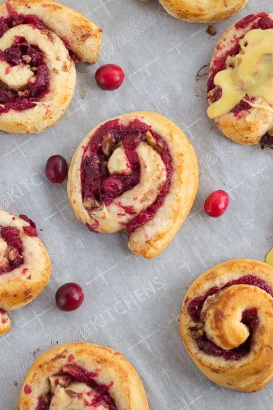 Freshly baked cranberry orange cinnamon rolls sitting on baking sheet and parchment paper.