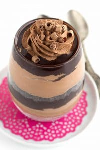 Close up of a glass filled with layers of chocolate trifle on a pink doily and white saucer