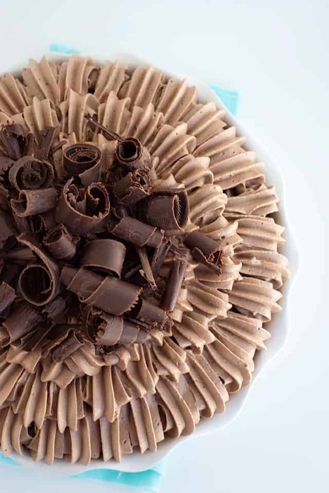 overhead shot of a chocolate cream pie in a white pie plate with the chocolate whipped cream piped on to and large chocolate curls.