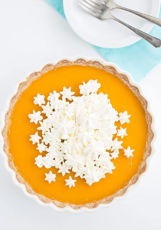 overhead shot of a pichuberry tart in a white tart pan with a stack of white plates.