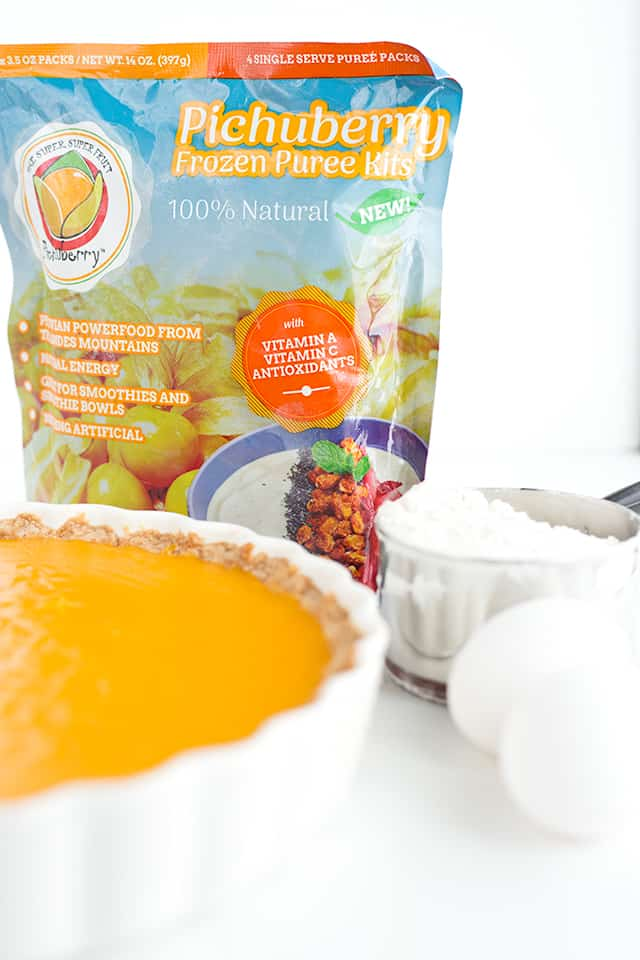 Pichuberry puree bag in focus with eggs, flour, and the pichuberry tart around the bag.