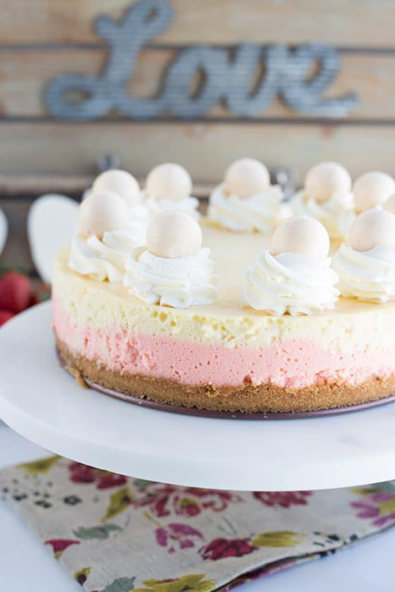 Full strawberries and cream cheesecake sitting on a marble cake stand