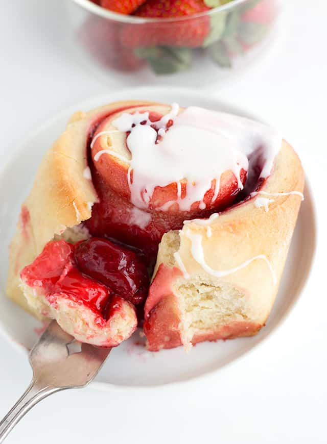A fork full of the strawberry sweet rolls is showing. It's a single sweet roll on a white plate with glaze on top.