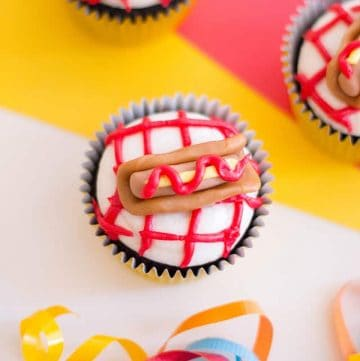 three hot dog cupcakes with a yellow, red, white background
