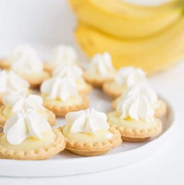Mini banana cream pies on a white plate with bananas in the background