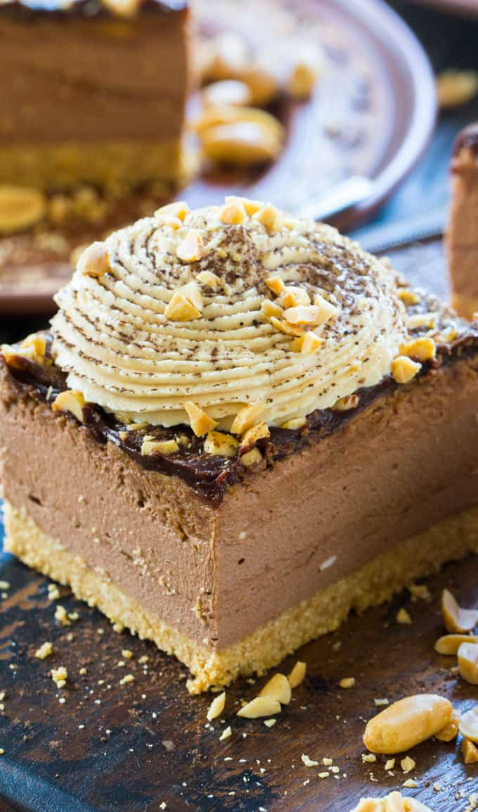 a piece of chocolate peanut butter cheesecake topped with whipped cream and peanuts