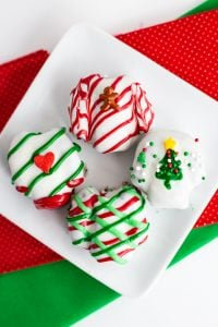 Ugly Sweater OREO Cookie Balls on a white plate with red and green fabric