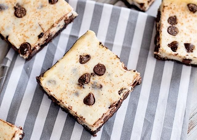 eggnog cheesecake bars with chocolate chips on a gray and white fabric