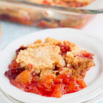 strawberry mandarin orange dump cake on a plate with glass pan