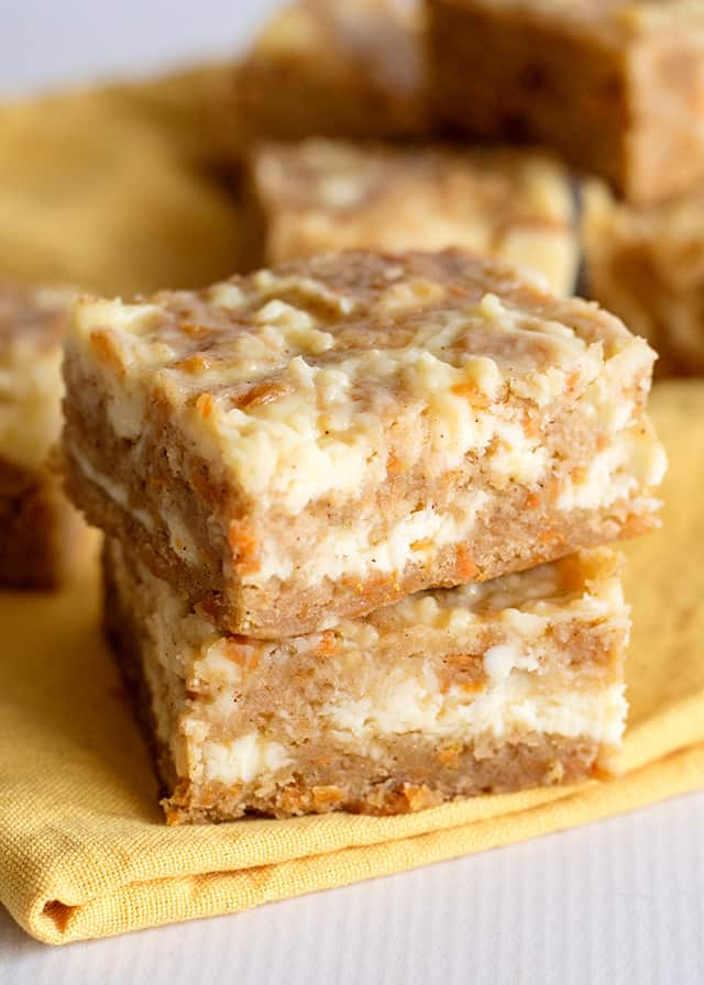 two carrot cake bars stacked on yellow linen