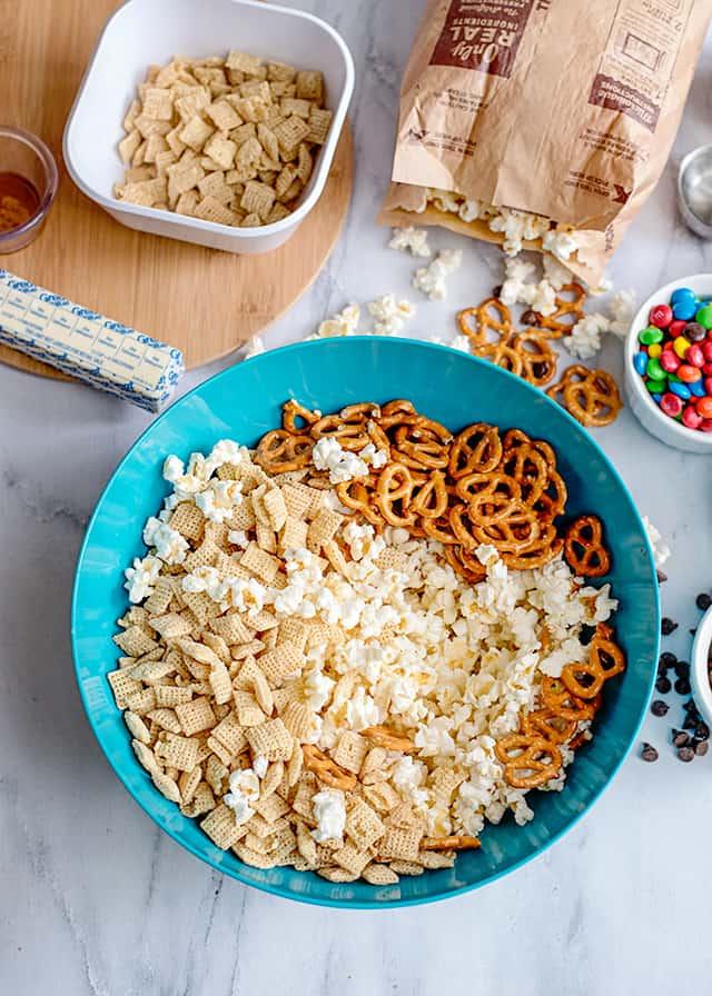 blue bowl of cereal, pretzels, and popcorn