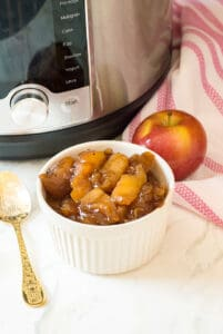 white ramekin with instant pot cinnamon apples and gold spoon