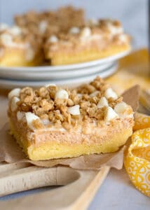 slice of sweet potato cheesecake bars on paper with yellow linen