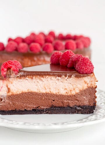 slice of chocolate raspberry cheesecake on a white dessert plate