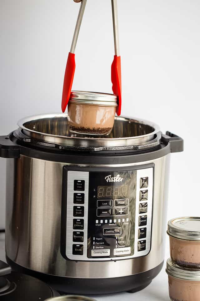 pulling a peppermint hot chocolate cheesecake in a jar out of the Souspreme Multi Pot with tongs