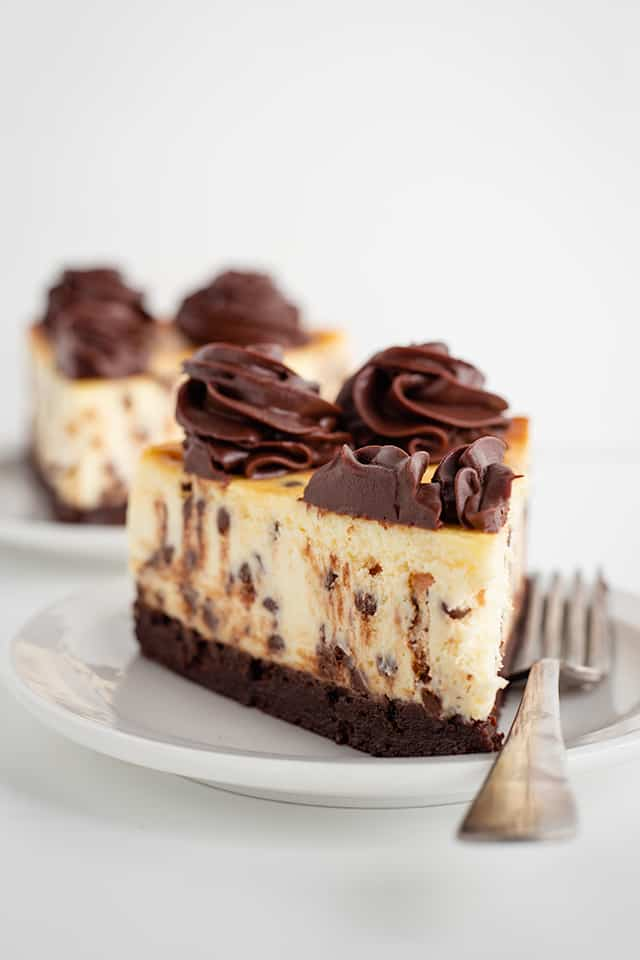 slice of brownie chocolate chip cheesecake on white dessert plate with a fork