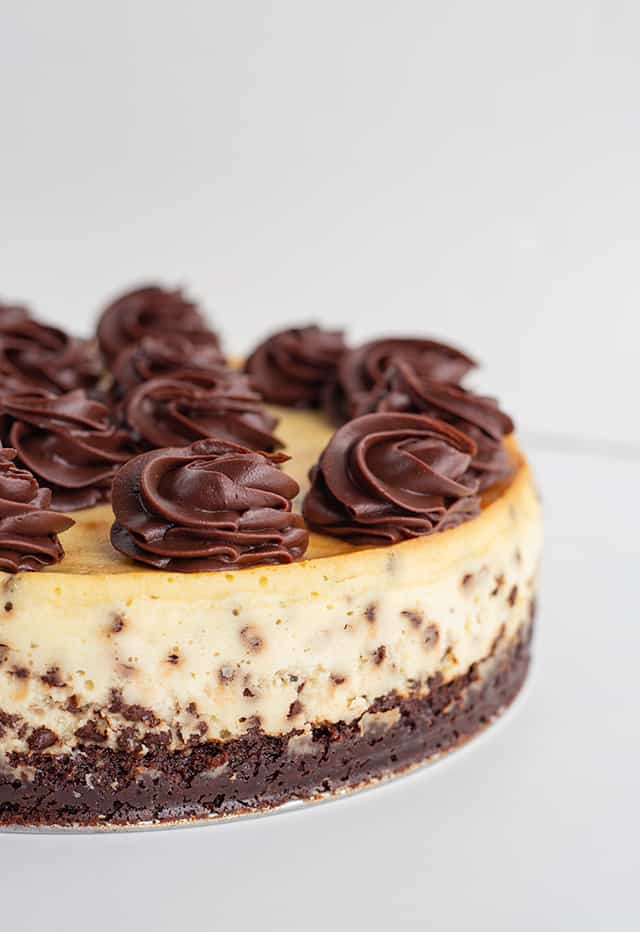 brownie chocolate chip cheesecake with swirls of ganache on a metal plate