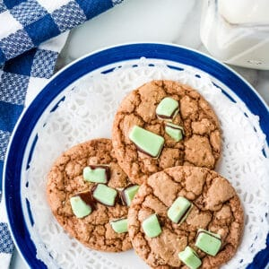 three andes mint cookies on a blue plate with a paper doily