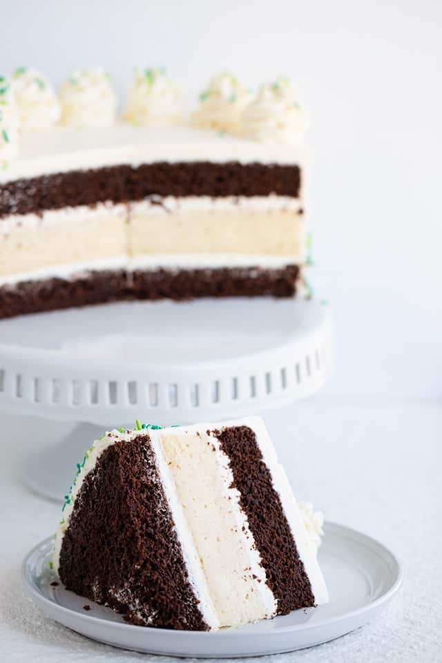 slice of cheesecake cake with the cake on a cake plate in the background