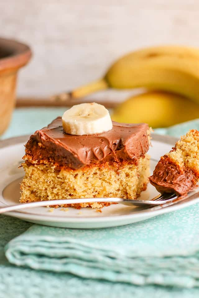 a forkful of banana cake on a plate